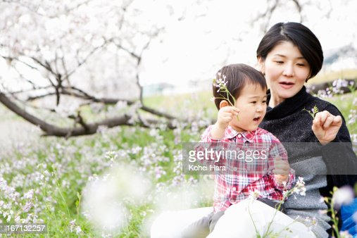 mother and son having a picnic in the flower field : Stock Photo
