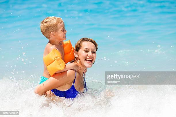 Mother and son having fun on sea waves