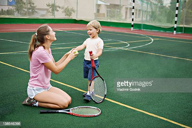 A mother and son having fun on tennis court