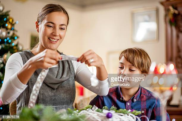 Mother and Son having Fun Preparing the Christmas Wreath