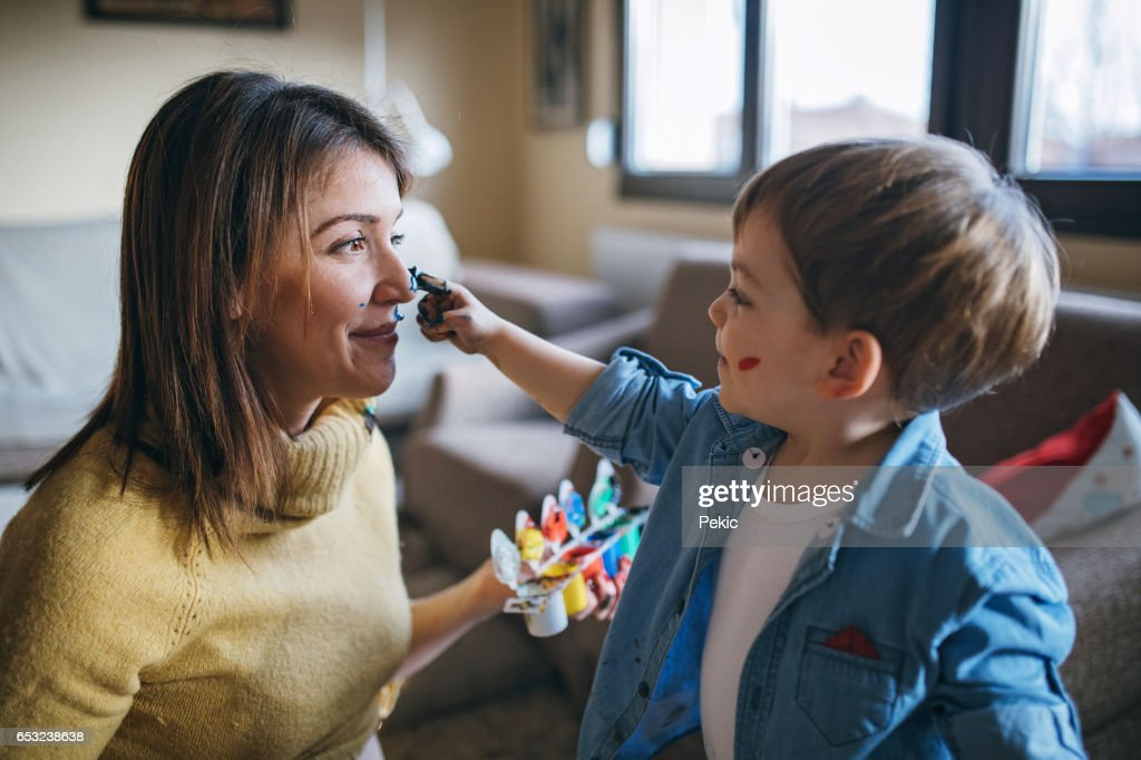Mother and son having fun with finger paint : Stock Photo