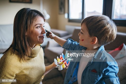 Mother and son having fun with finger paint : Stockfoto