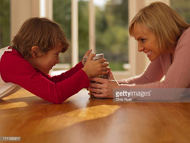 Mother and son hold at jar full of coins