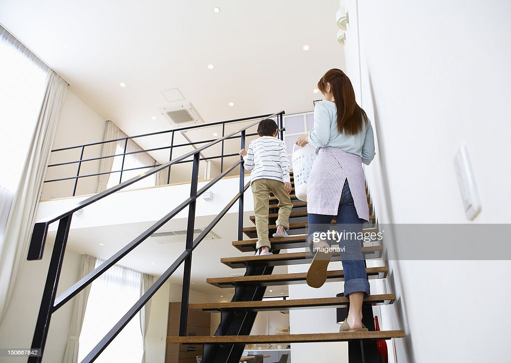 Mother And Son Holding A Laundry Basket And Going Up Stairs : Stock Photo