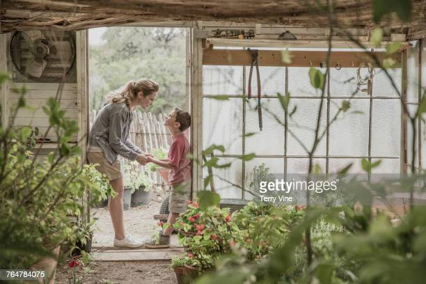 Mother and son holding hands in greenhouse doorway