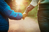 mother and son holding hands in sunset nature, parenting concept