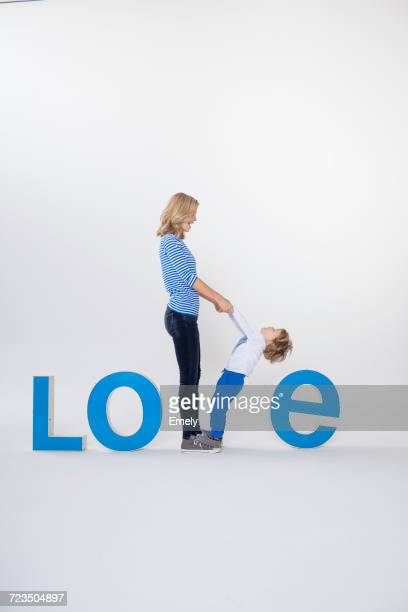 Mother and son holding hands, standing between three-dimensional letters, creating the word LOVE