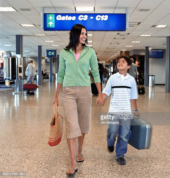 Mother and son (9-11) holding hands while walking through airport