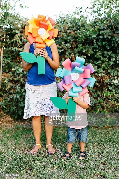 Mother and son holding home-made cardboard flowers in front of their faces