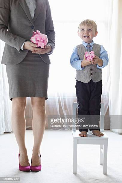 Mother and son holding piggy banks