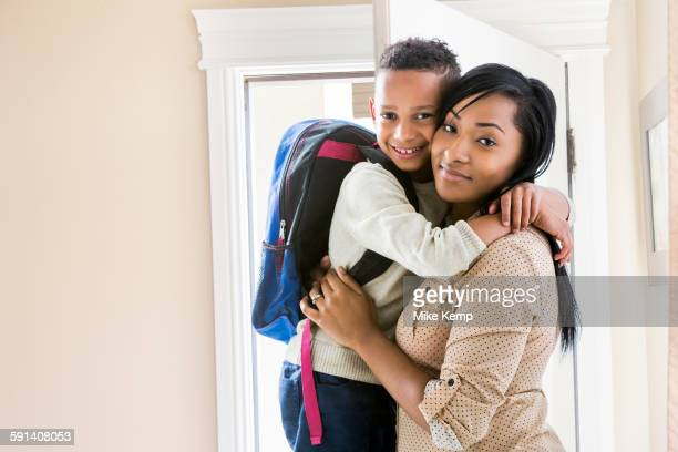 Mother and son hugging at door