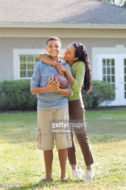 Mother and son hugging in backyard