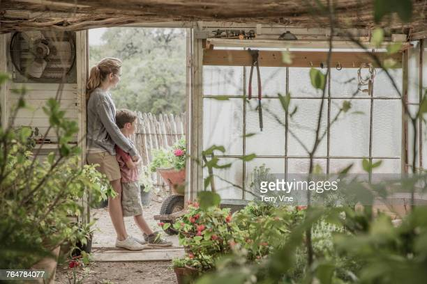 Mother and son hugging in greenhouse doorway