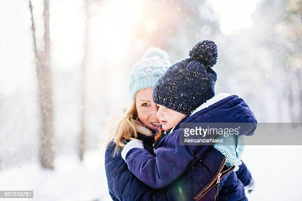 Mother and son hugging on the snow