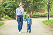 Young mother and her cute little son walking in a park