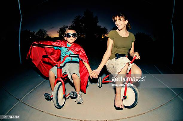 Mother and son in cape riding tricycles in the dark