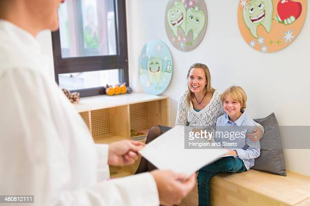 Mother and son in dentists waiting room