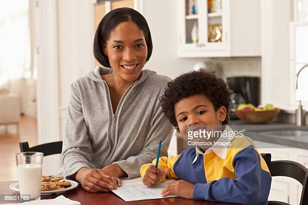mother and son in kitchen doing homework