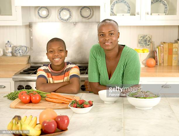 Mother and son (10-11) in kitchen, smiling, portrait