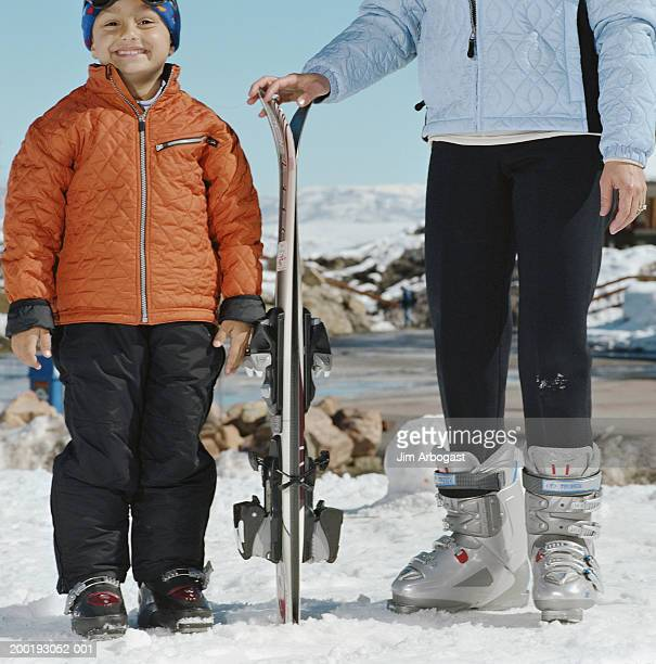 Mother and son (4-6) in snow field, woman holding skis