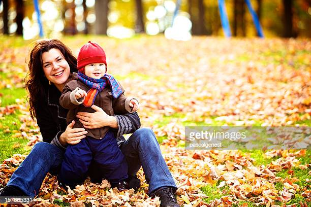 Mother and son in the park with leaves on the ground