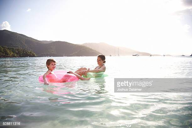 Mother and son in water on inner tubes