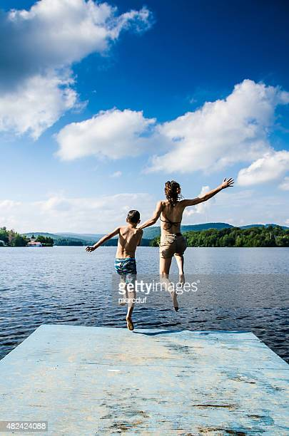 Mother and son jumping in lake from dock