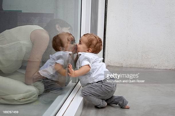 Mother and son kissing through glass