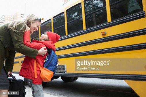 Mother and son laughing and hugging next to school