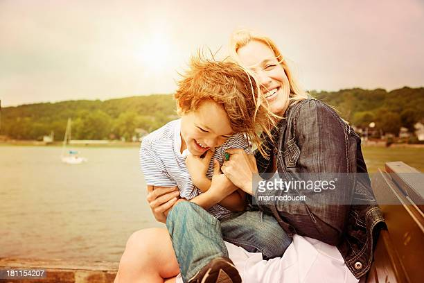 Mother and son laughing on a bench at sunset.