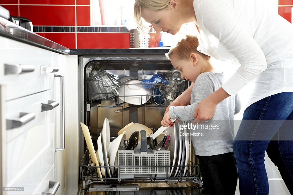 Mother and son loading dishwasher