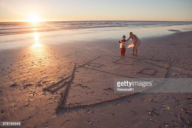 Mother and son looking at building plans on beach with drawn house in the sand