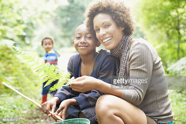Mother and son looking at fern leaf