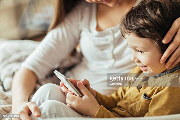 Mother and son looking at mobile phone