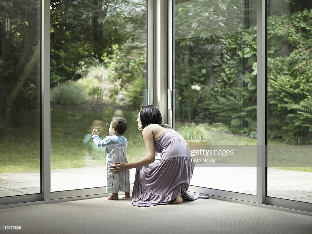 Mother and son looking out window : Stock Photo