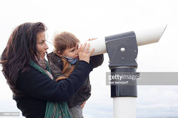 Mother and son looking through telescope
