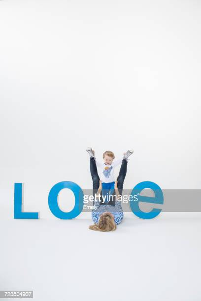 Mother and son lying on floor between three-dimensional letters, creating the word LOVE