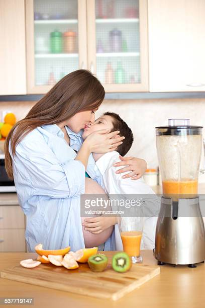 Mother and son making fresh orange juice