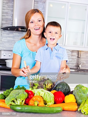 Mother and son making salad surrounded by vegetables : Stock Photo