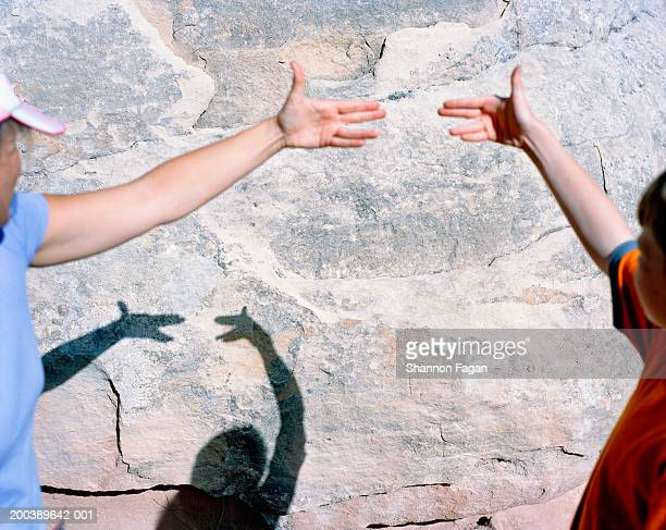 Mother and son (11-13) making shadow puppets on rock wall