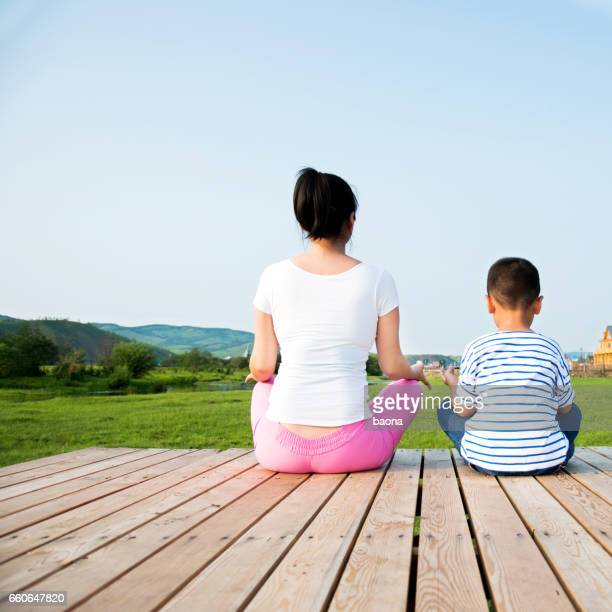 Mother and son meditating in the nature