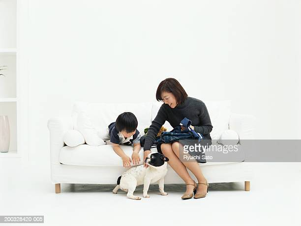 Mother and son (3-4) on sofa playing with dog