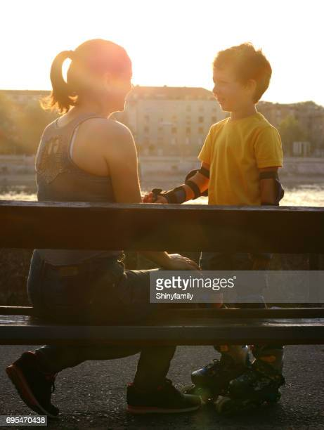 Mother and son on the bench by the river.