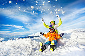 Mom and child with ski outfit mask and helmet sit and throw up snow