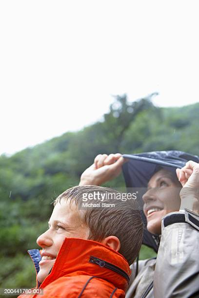 Mother and son (11-13) outdoors in rain, looking towards sky, smiling