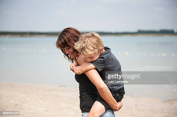Mother and son piggyback riding on beach