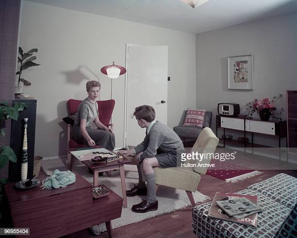 A mother and son play Scrabble in the living room of their home circa 1955 A copy of 'Picture Post' magazine lies on a chair nearby