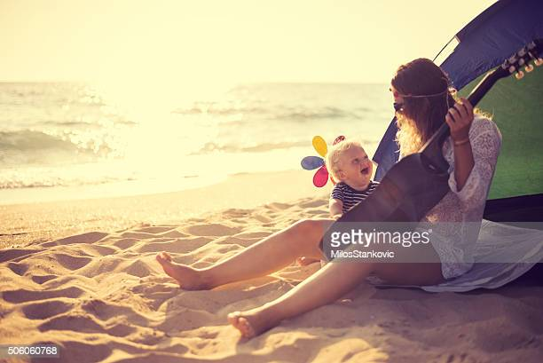 Mother and son playing a guitar on the beach