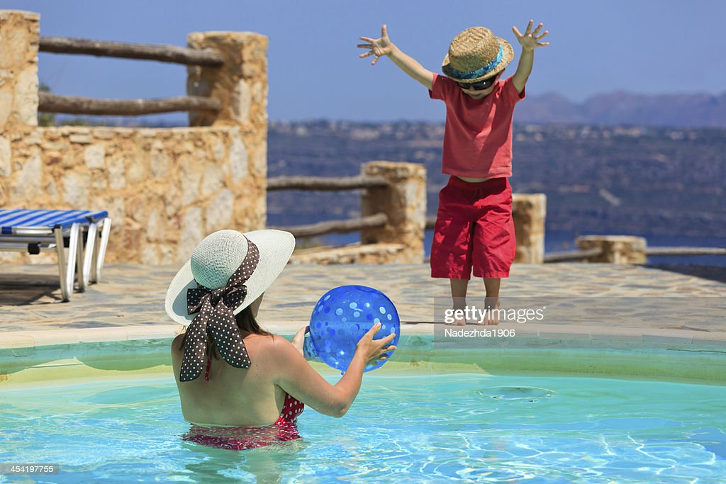 mother and son playing at the pool : Stock Photo
