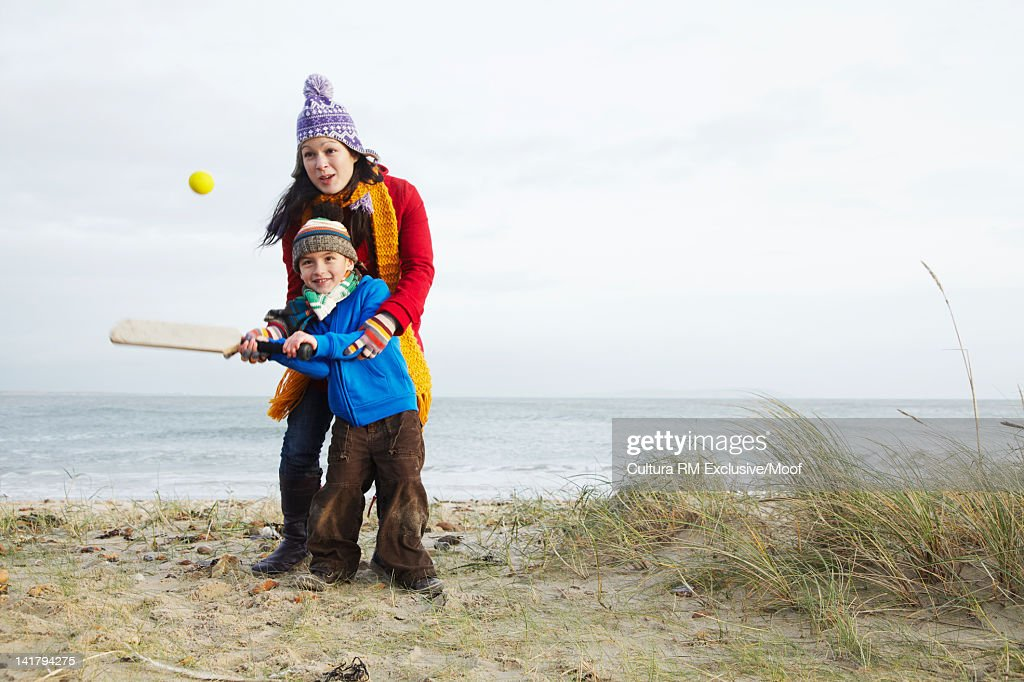 Mother and son playing cricket on beach